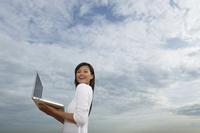 Young woman holding open laptop - Yukmin