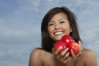 Young woman holding apples and smiling - Yukmin