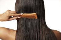woman pulling comb through her hair - Vivek Sharma