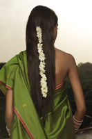 woman wearing sari with strand of jasmine blossom in her hair - Vivek Sharma