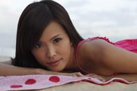 Woman lying on towel on sand - Yukmin