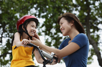 Young woman fastening bike helmet on girl - Yukmin