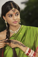 woman wearing sari and decorated with henna tattoo, traditional jewelry and bindi - Vivek Sharma