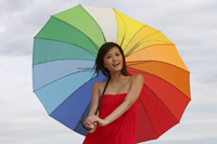 Young woman standing under bright umbrella - Yukmin