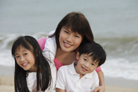 Young woman hugging boy and girl on beach - Yukmin