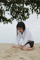 Young girl playing in the sand near ocean - Yukmin
