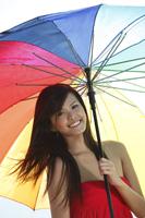 Young woman standing underneath umbrella - Yukmin