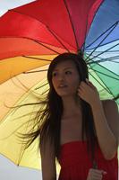 Young woman standing under bright umbrella - Yukmin