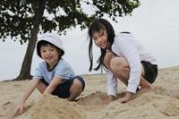 boy and girl playing in sand near ocean - Yukmin