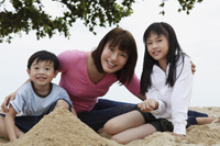 Young woman with boy and girl playing in sand - Yukmin