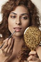 Young woman painting her lips - Vivek Sharma