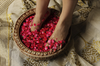 woman's feet soaking in rose petals and rose water - Vivek Sharma