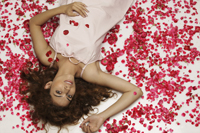 woman lying surrounded by rose petals - Vivek Sharma