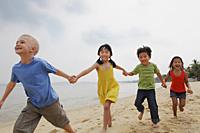 Four kids running down the beach holding hands. - Yukmin
