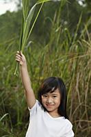 Girl holding leaves in air. - Yukmin