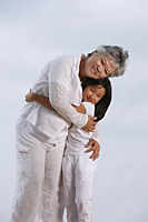 Older woman and young girl hugging. - Yukmin