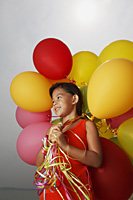 Girl holding balloons looking away. - Yukmin