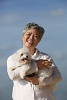 Older woman holding dog. - Yukmin