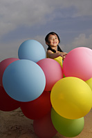 Young girl smiling at camera holding balloons. - Yukmin