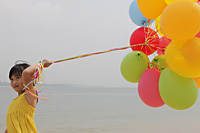 Young girl holding balloons. - Yukmin