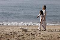 Older woman walking dog with young girl. - Yukmin