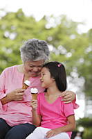Older woman and young girl eating ice cream. - Yukmin