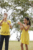 Older woman and young girl playing with bubbles. - Yukmin