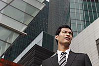 business man in suit standing among tall buildings - Yukmin