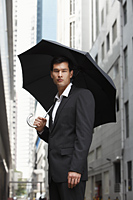 businessman holding umbrella - Yukmin