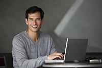 man working on laptop, smiling at camera - Yukmin