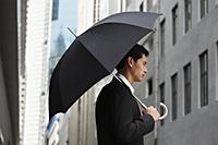 side profile of businessman holding umbrella - Yukmin