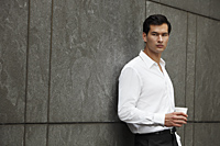 man in white shirt holding a cup of coffee, leaning against wall - Yukmin
