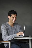 man working on laptop, smiling - Yukmin