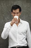 man in white shirt drinking coffee - Yukmin