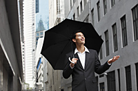 businessman holding umbrella, looking up into the sky - Yukmin