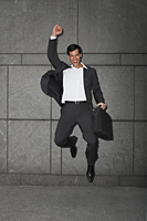 businessman holding briefcase, jumping with arm raised - Yukmin