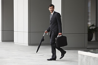 business man in suit carrying briefcase and umbrella - Yukmin
