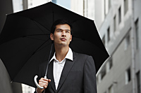 businessman holding umbrella, looking up - Yukmin