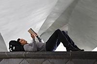 man lying down laying at back pack, reading a book - Yukmin