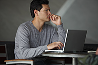 side profile of man working on laptop, thinking - Yukmin