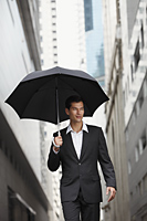 businessman holding umbrella - Yukmin