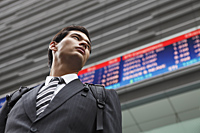 businessman standing before stock exchange - Yukmin