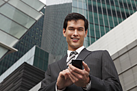 business man in a suit using mobile phone - Yukmin