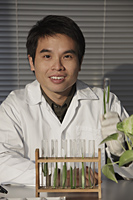 Scientist holding a test tube. - Yukmin