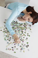 top view of young woman putting  puzzle together - Yukmin
