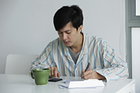 Young man working on bills at home - Yukmin