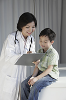 Female doctor giving a young boy a check up - Yukmin
