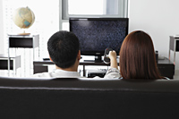 Back view of young couple watching TV at home - Yukmin