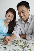 Young couple putting puzzle together and smiling - Yukmin