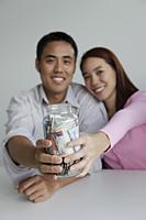 Young couple holding jar of money - Yukmin